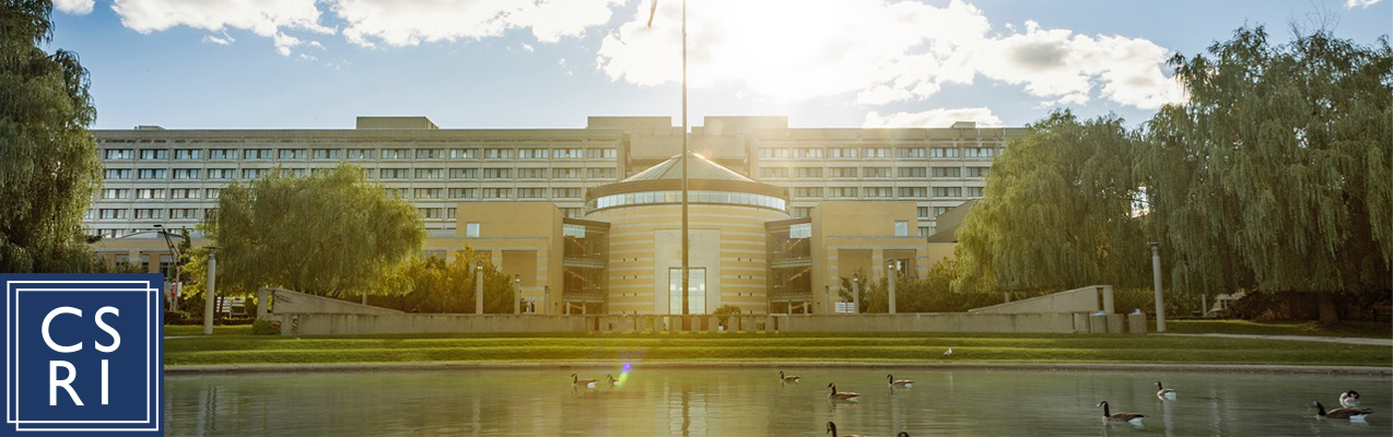 "A wide-angle picture of Vari Hall. Ducks are in the pond and the sun is shining. In the lower, right corner is a logo with the Journal's initials ""CSRI""."